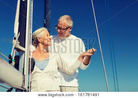 sailing, age, tourism, travel and people concept - happy senior couple holding hands on sail boat or yacht deck floating in sea