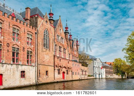 Old buildings along beautiful canals on a sunny spring day in Bruges, Belgium