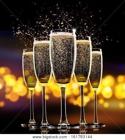 Group of glasses of champagne over blur spots lights background. Celebration concept