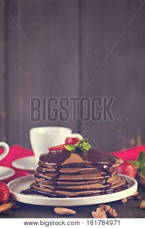 chocolate pancakes with chocolate sauce and strawberries. coffee. breakfast