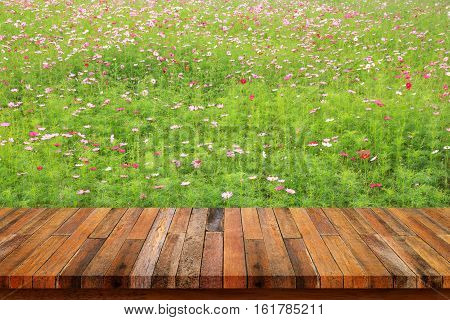 Wood table top with background of pink flowers.