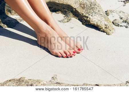 Pretty woman feet with red pedicure: relaxing on sand. Holiday, vacation, spa, summer: concept.