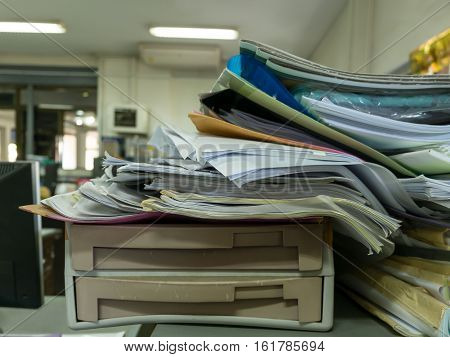 Pile of documents on desk stack up high at workplace
