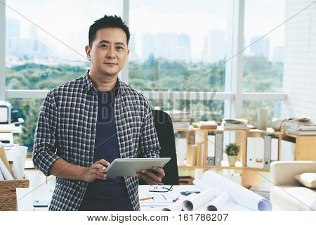 Portrait of professional Singaporean architect with tablet computer