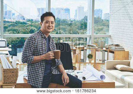 Smiling engineer having coffee break in architecture bureau