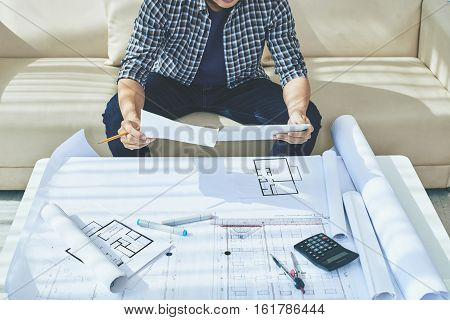 Architect reading requirements specification before working with blueprint