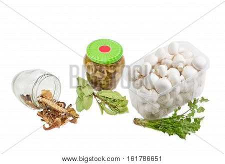 Dried boletus pickled button mushrooms in glass jar fresh uncooked button mushrooms in a transparent plastic tray and branches of a dried bay leaf and fresh coriander on a light background