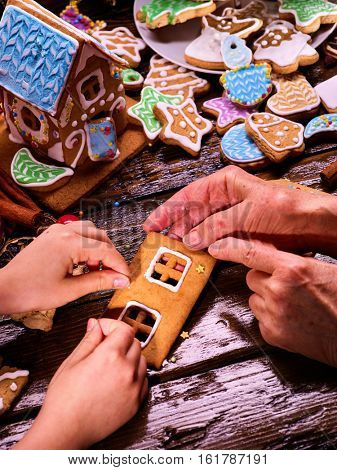 Gingerbread hause make by grandma and crandchild hands. Sweet course for Christmas holiday. Family handicraft before Xmas party. For idea childish cooking . Teaching children to cook. poster
