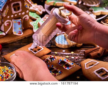 Gingerbread hause making by child hands. Sweet course for Christmas holiday. Kid handicraft before Xmas party. Use for recipe and master class childish cooking . Teaching children to cook.