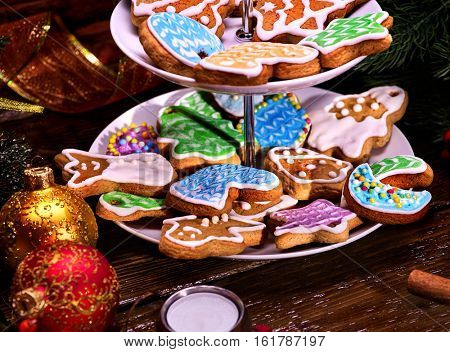 Christmas Cookie of Gingerbread. Sweet course of confection on dessert stand. Two level of pastry. Xmas ball foreground. Candle on wooden table. Colourful biscuit on plate. Holiday food in restaraunt.