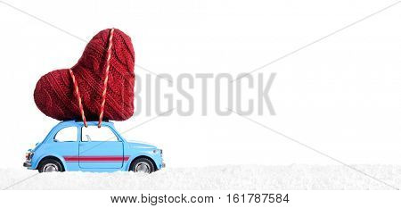 Blue retro toy car delivering heart for Valentine's day on white background