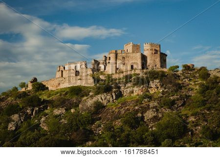 Beautiful Spanish old castle over a hill with a amazing sky of background