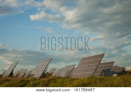 Solar panels in the landscape with a cloudy sky of background