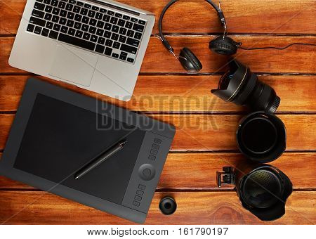 Photography staff on wooden table view from top. Modern photography equipment gear