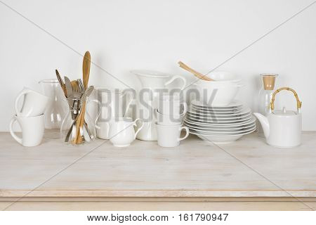 Set of various white dishware and cutlery on wooden table