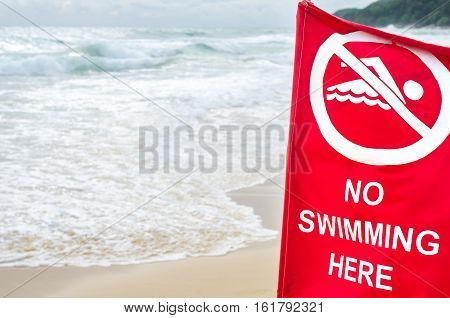 No swimming here sign on storm beach background. Copy space of nature and environment.