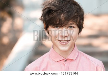 Funny teenage boy 14-16 year old with messy hairstyle posing outdoors. Looking at camera.