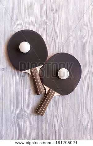 black racket for ping pong ball on gray wooden background top view