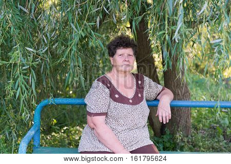 Mature woman with curly hair sitting on the bench under weeping willow