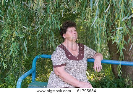 Mature woman with curly hair sitting on the bench weeping willow