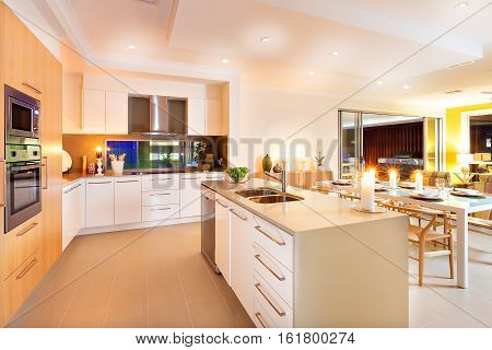 Roomy interior has illuminated with yellow light spreading over the whole kitchen and dining area The flashing candles on the center of the kitchen and top of the table giving an extra shiny look to the area