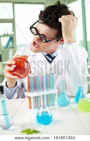 Tousled chemist looking at flask with chemical