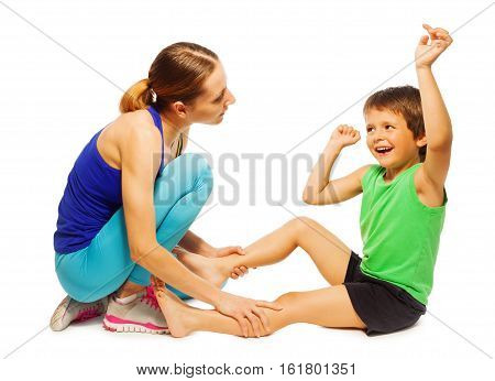 Portrait of happy kid boy sitting on the floor and doing physical exercises with female trainer, isolated on white