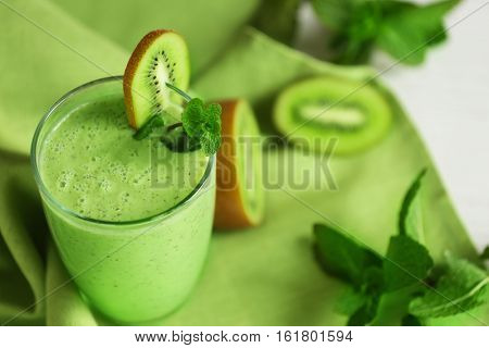 Glass of kiwi smoothie on green napkin