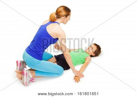 Young female trainer teaching little sportsman making physical exercises on the floor, isolated on white