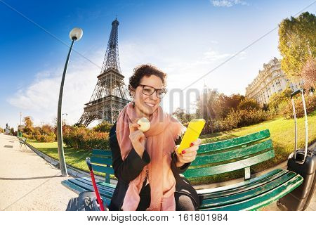 Happy female tourist eating traditional French cookie macaron, sitting on the bench with smart phone in her hands against the Eiffel Tower