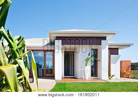 Front of the Modern villa with a lawn and blue sky The house has a small green grass of the ground and the concrete yard front of it. The facade has a tall and white vase with an ornamental plant. There are huge two pillars under the roof. There is a wood