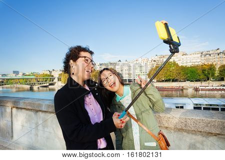 Two cheerful female tourists taking selfie photo with stick at the embankment of the Seine River, Paris