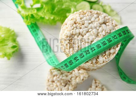 Round rice crispbreads with measuring tape and lettuce, closeup