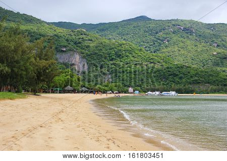 beautiful beach of Vietnam is surrounded by mountains, yellow sand, clear sea water, away vacationers people, ships, mountains covered with greenery, Paradise place to stay