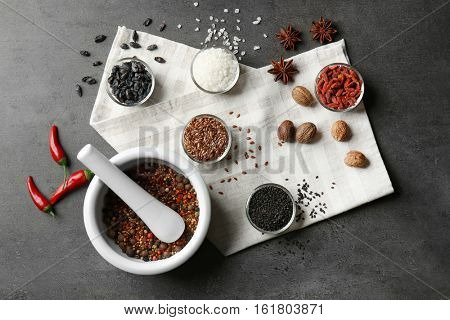 Composition with different spices and mortar on gray background