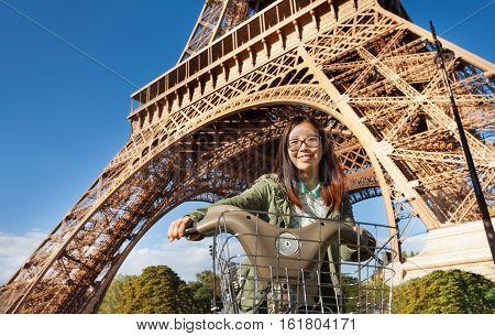 Pretty young Asian woman riding rental bike near Eiffel Tower, Paris