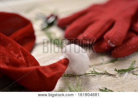 closeup of a santa hat, a pair of cozy red gloves, some twigs of pine tree and a twig of holly in the background, on a rustic wooden table