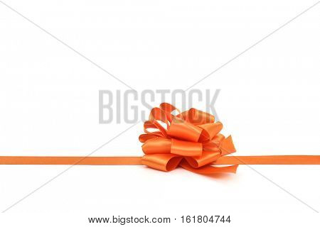 an orange satin gift ribbon bow on a white background, with a negative space