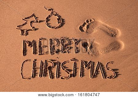 some foot prints, the text merry christmas and the sketch of a christmas tree and a christmas ball carved in the sand of a beach
