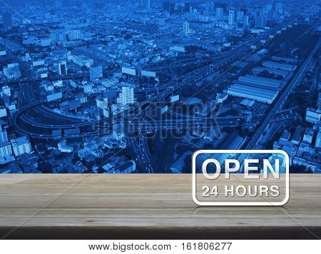 Open 24 hours icon on wooden table over aerial of modern city tower street and expressway