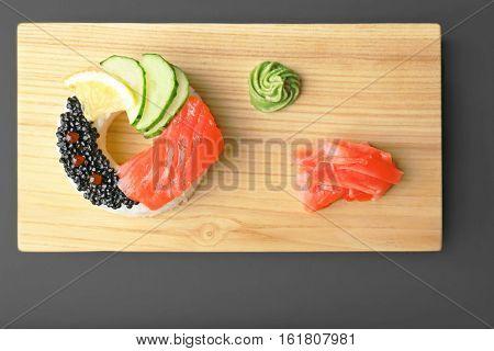 Sushi doughnut on wooden cutting board, top view
