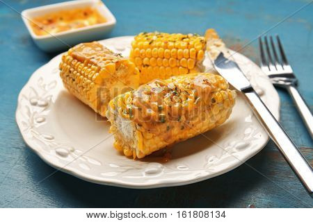 Plate with cut tasty grilled corncobs, sauce and herbs on wooden table, close up view