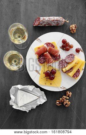 Glasses with white wine, grape, wurst and cheese on grey background