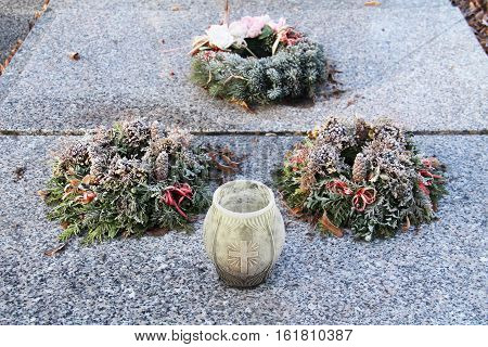 three wreaths and a lantern on the grave covered with hoarfrost