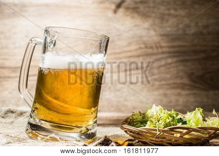 Big mug with beer foam stands on linen cloth with hops on table