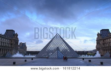 PARIS, FRANCE, January 13: The Louvre Pyramid under the mystical sky. It serves as the main entrance to the Louvre Museum. Completed in 1989 it has become a landmark of Paris.