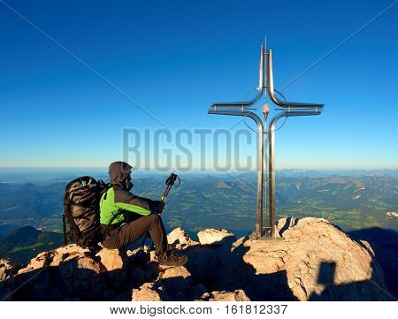 Tired Hiker Sit Bellow Crucifix On Mountain Peak. Iron Cross At Alps Mountain Top.