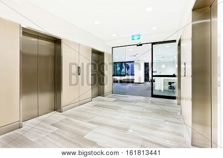 Modern silver elevator in a luxury building with open glass door to another area