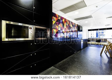Luxury kitchen style with two microwaves fixed to the wall next to the colorful wall tiles which illuminated by sunlight