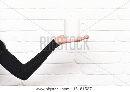 female tender hand in slim black sleeve holding white cup with tea or coffee on brick wall background copy space